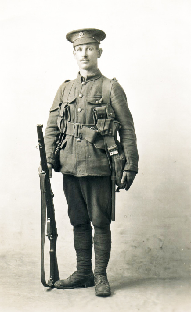 James Bird, recipient of a care parcel, poses in his Service Uniform possibly immediately after mobilisation. The equipment is of the new pattern webbing material and he carries a .303 inch Short Magazine Lee Enfield Rifle. The uniform colour is khaki is of durable material The tunic is ill fitting and newly worn - note the stiffness of the skirt of the garment. His hat is of the pre-war style with its crown stiffened by a wire band. The style swiftly lost appeal in combat conditions because the crown made the wearer conspicuous even when the body had been expertly camouflaged. The band was usually discarded and the profile of the crown manipulated to soften the outline.