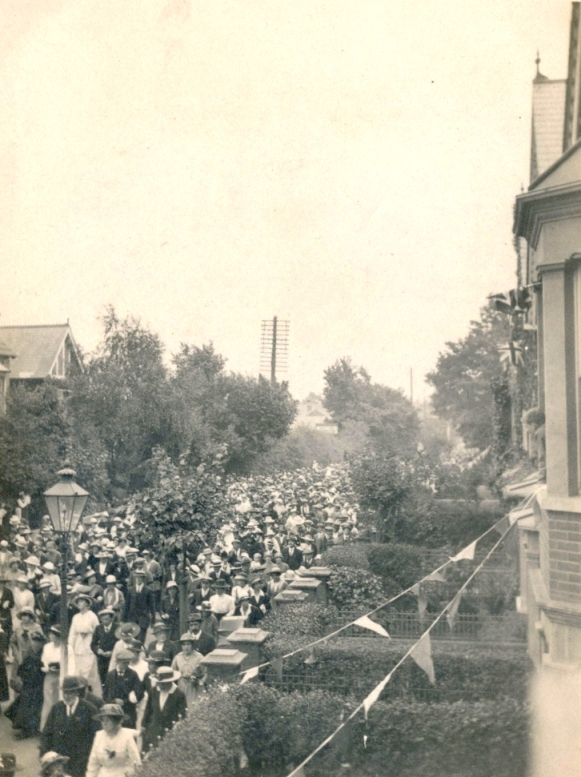 Mass parade of people dressed in 'Sunday best' – note the women in long dresses still and everyone wears a hat.